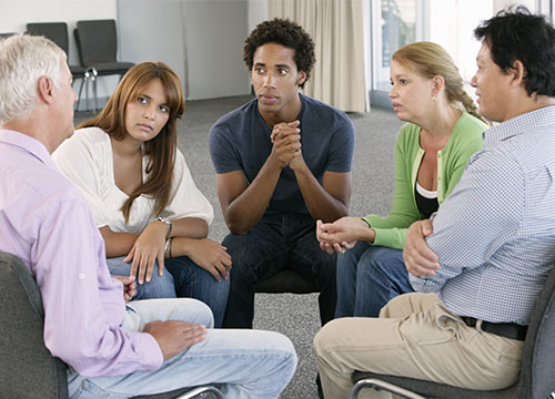 A group of people sitting in circle having a conversation'